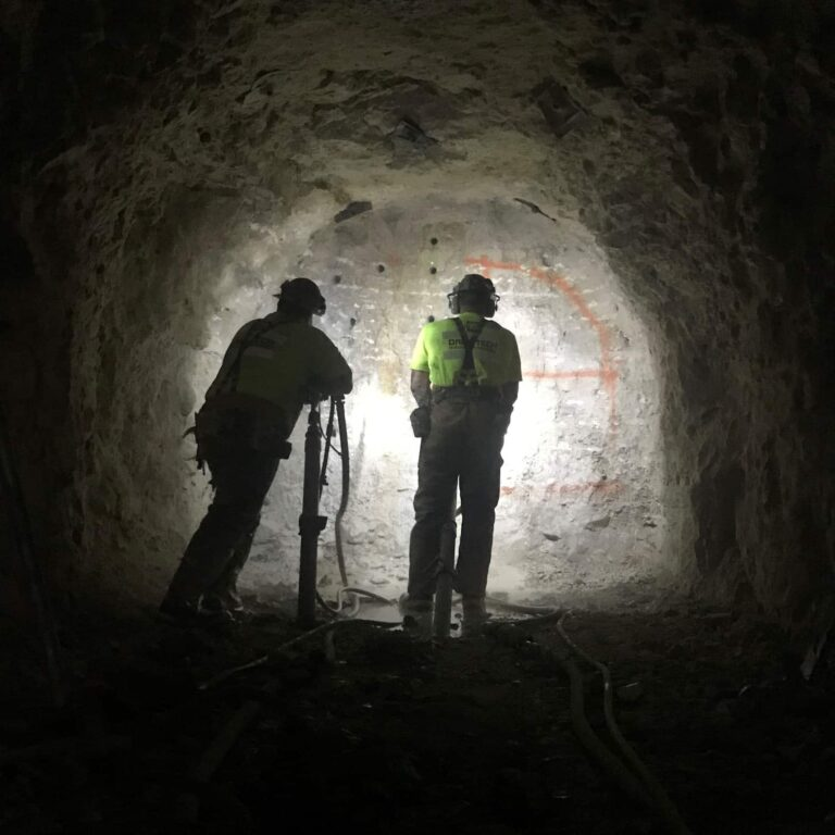 Miners drilling holes in rock prior to placing explosives
