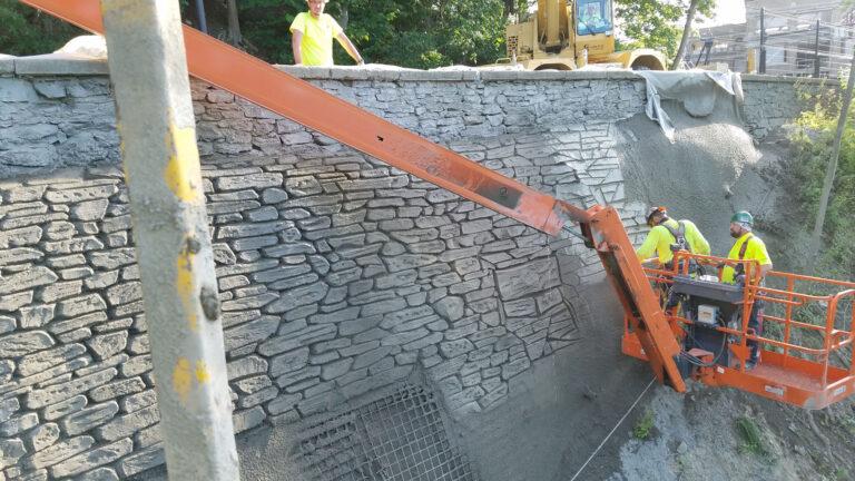 Workers hand sculpting shot-crete facing for retaining wall repair